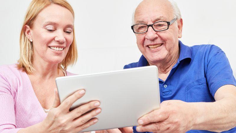 Frau und älterer Mann schauen auf Tablet