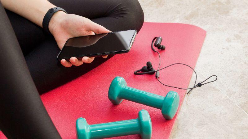Training zu Hause mit Smartphone und Hanteln